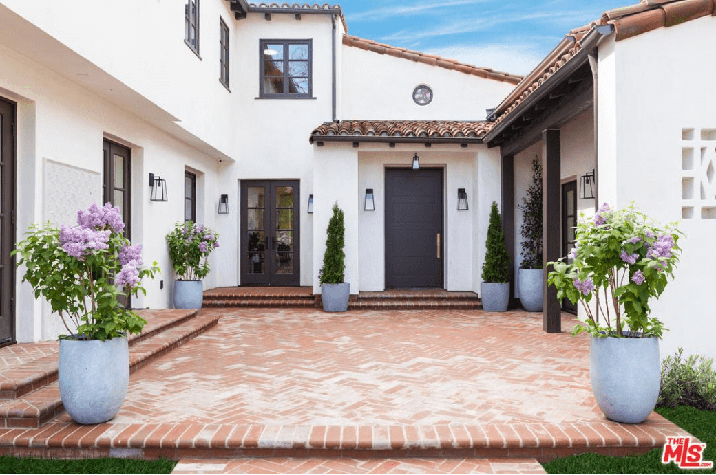 The worn bricked floor and steps pair perfectly with the white exteriors and dark wooden doors flanked by wall-mounted lamps. The bluish stone pots of the plants and flowers also stand out against the brick floor that reflects the clay-tiled <a class=