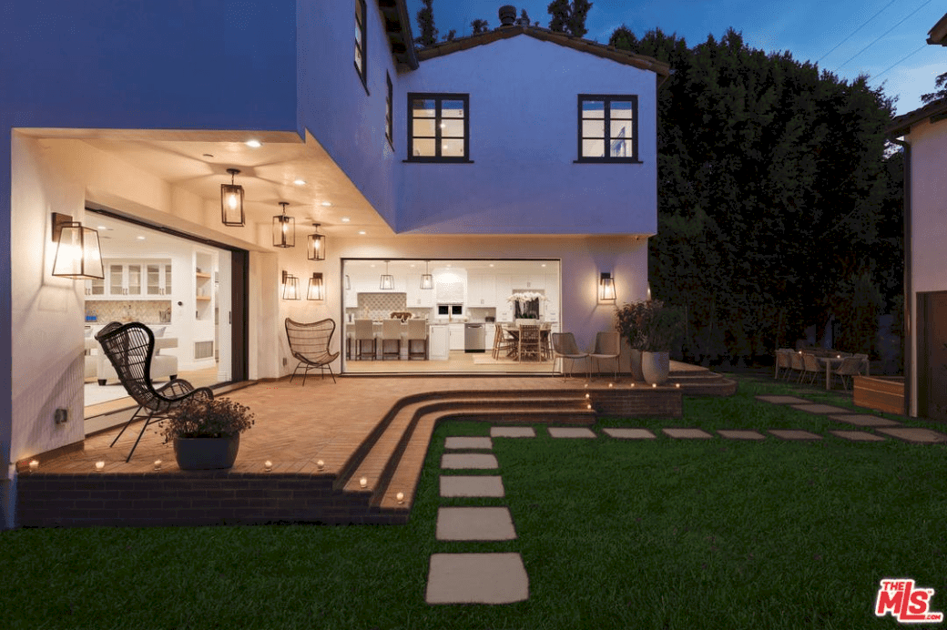 The bricked floor of the patio is illuminated by yellow light from wall-mounted lamps, pin lights, and semi-flush mount lighting. The patio ends into steps toward the Bermuda grass lawn that is paved with square stone steps leading to tall trees lining the walls looking over an outdoor dining area.