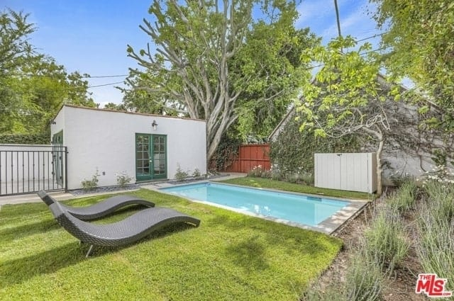 This is a lovely backyard that features a small rectangular pool surrounded by well maintained Bermuda grass where a pair of woven lawn chairs face the pool. The white tool shed beside the pool is a nice contrast to the tall <a class=
