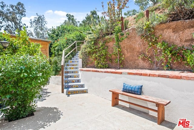 The beautiful pairing of the terracotta ledge with the colorful patterns of the winding stairs gives this backyard a distinctive Spanish flair. This is further enhanced by the well-maintained variety of plants and a rustic long bench placed against a white wall.