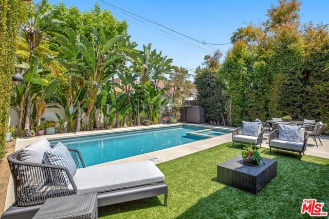 The palm trees lining one of the walls give this backyard a tropical vibe. This is paired well with the rectangular pool and a carpet of Bermuda grass on the side where a set of outdoor sofas are placed. There is also a set of garden table and chairs next to the other wall that is lined with tall trees.