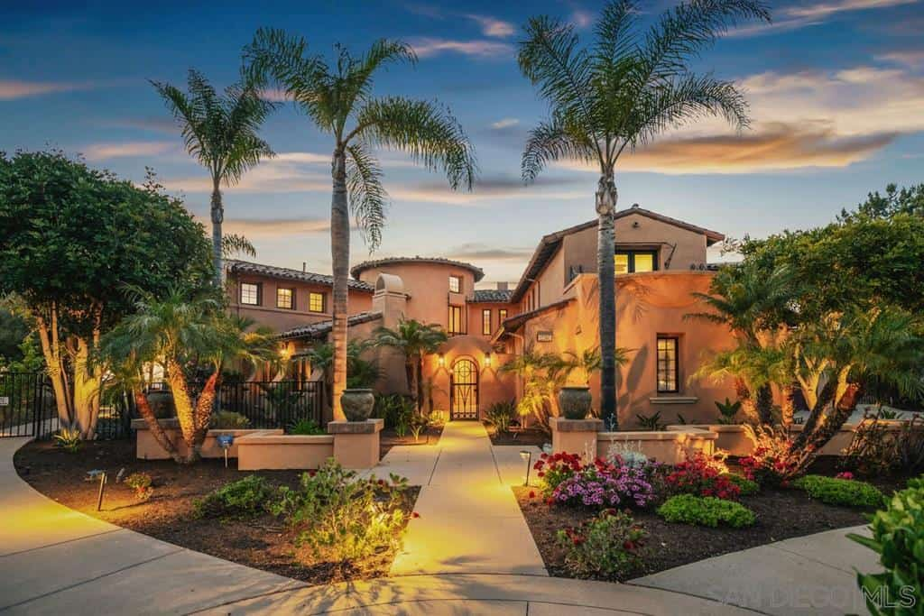 The beautiful symmetry of the Spanish landscaping is the centerpiece of this front yard with its pair of low stone walls, large urns, and cement walkways. Even the tropical trees are strategically placed to pair with each other and stand guard over the colorful flowers illuminated by warm yellow spotlights.