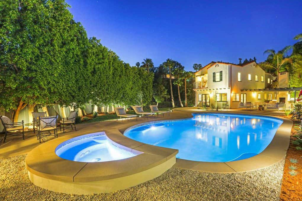 The centerpiece of this backyard is the massive curving pool with a matching jacuzzi. These two are fitted with gray stone walkways and lined with tall trees for privacy. The poolside lawn chairs match well with the cushioned garden set illuminated by spotlights placed all throughout the area.