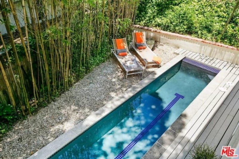 A peculiarly long and narrow pool maximizes this landscape and sets the theme. This theme is mirrored on the planked floor beside the pool and even the Bamboo trees lining the other side. The Bamboo trees give shade to the two poolside lawn chairs on the graveled of the pool.