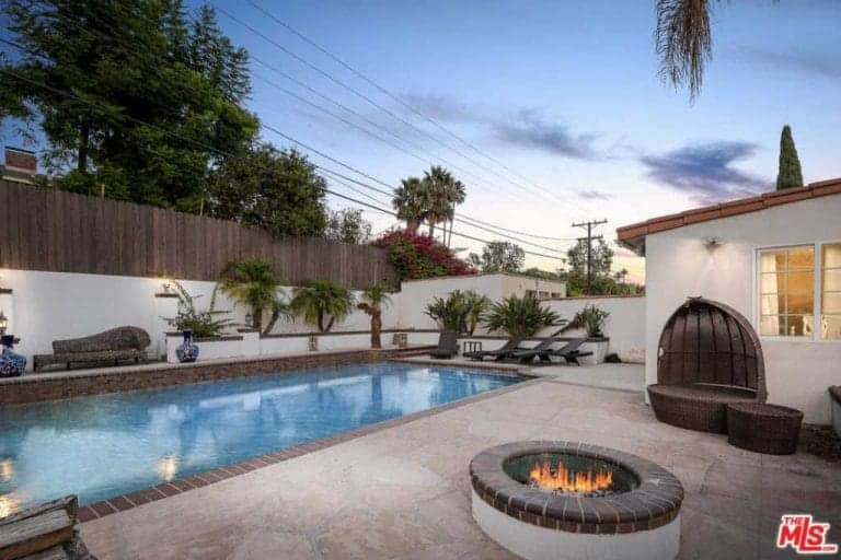 A circular open firepit stands in the middle of the stone floor on one side of the rectangular pool that shares the same designs as the firepit. A dark woven outdoor chair faces the firepit while lawn chairs are placed near the end of the pool where tropical trees are planted.
