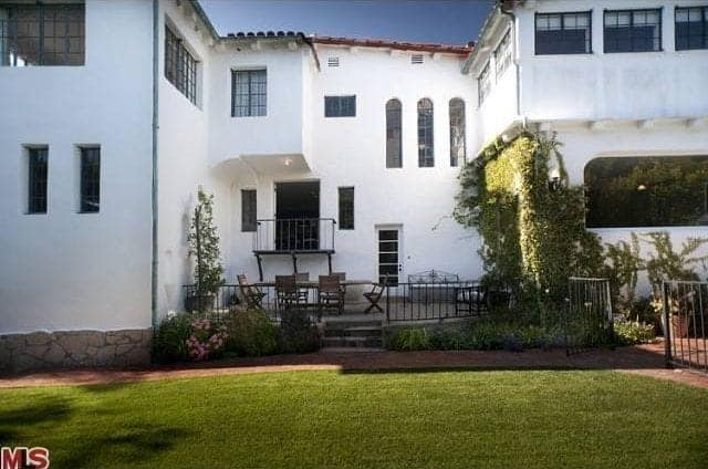 The outdoor dining area is surrounded by walls on three sides. One wall features the white exterior of the house with doors and windows. The next wall is almost filled with creeping ivy that overrun and yet aesthetically pleasing while the wall opposite it has colorful flowers. These are all open to a well-manicured lawn with terracotta walkways.