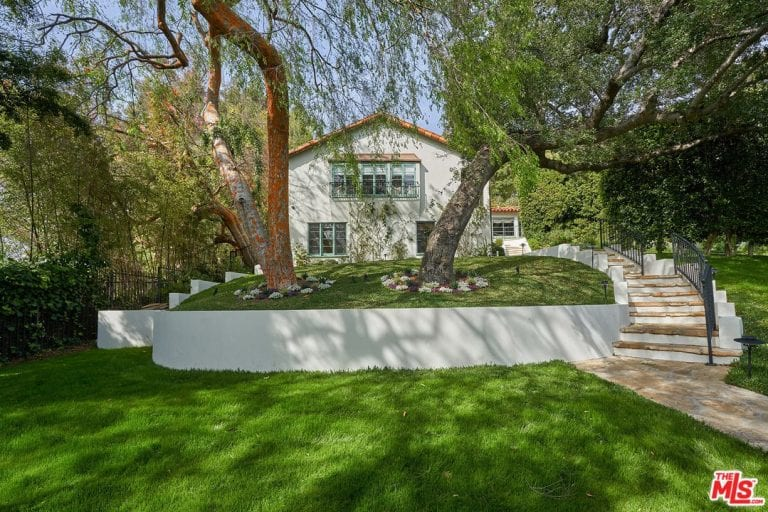 The exquisitely manicured grass lawn has a pair of stonework walkways on either side that leads to a stairway with dark iron railings. In the middle of two stairways, a single terrace ledge rises up from the lawn bearing two tall trees with their own bed.