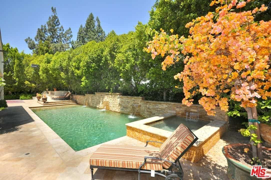The elegant stonework wall of the pool has a row of tall trees on top of it for privacy and isolation. The greenery of these trees is a nice contradiction to the beige theme of the rest of the pool area like the marble walkway and floor, lawn chair and the charming flowering tree shading it.