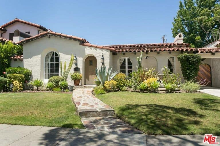 This is a Spanish landscape that takes pride in its simplicity mixed with tradition. A traditional stonework walkway leads to a traditional wooden door and arched walkway. This walkway is flanked with wall-mounted lamps ad potted plants. The simple grass lawn is separated from the walls of the house with a variety of succulents, cacti, and bushes.