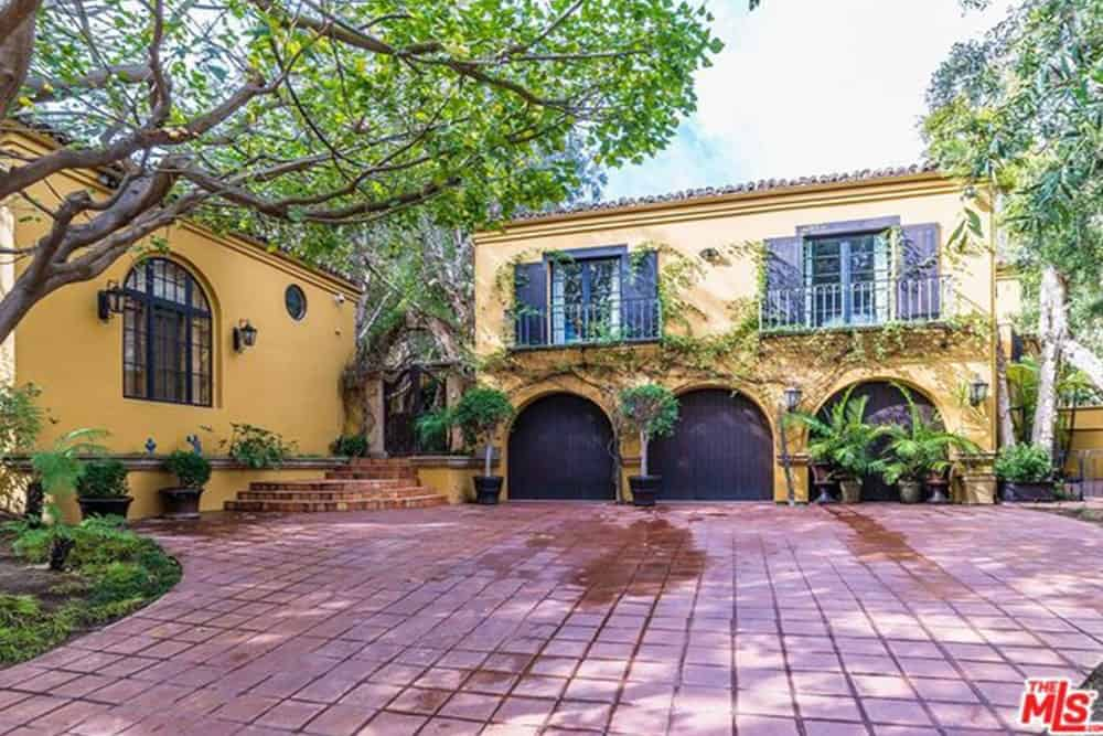 The terracotta driveway leads up to dark wooden garage doors with an arched shape. Creeping vines appear to have clung to the wall of the garage and arched walkway. Potted plants and tall trees line the surrounding walls of this driveway giving a relaxing environment.