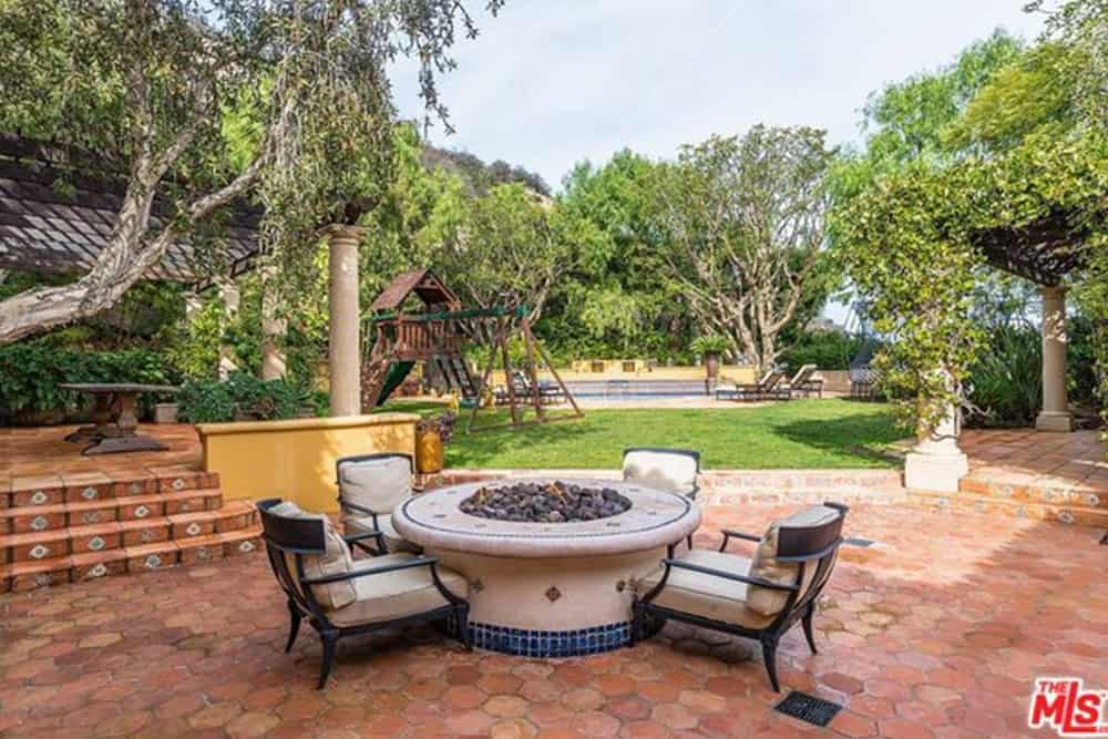 A circular fire pit that can double as a table is surrounded by white cushioned outdoor chairs. This garden set has a white color hue contrasting with the terracotta floor. A charming playground structure dominates the grass lawn of the poolside area.