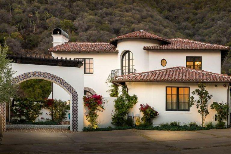 The Bougainvilla and plants along the outer white walls provide a dash of color and are a nice aesthetic partner for the French windows. An arched entryway doubles as a driveway and lined with colorful patterned tiles following the arched shape.