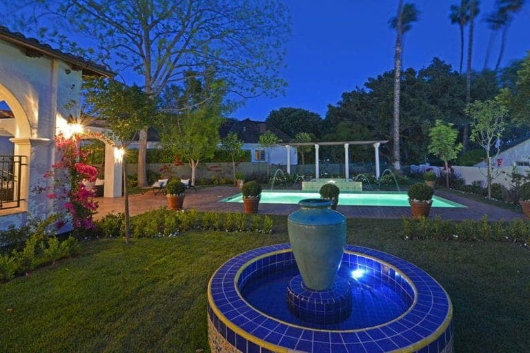 The brilliant fountain covered in blue and patterned tiles in the middle of the green grass lawn stands out against the scenery. This lawn is bordered with potted plants and small trees that separate it from the pool area with the terracotta floor illuminated by the brilliant pool lights giving off a bluish glow.