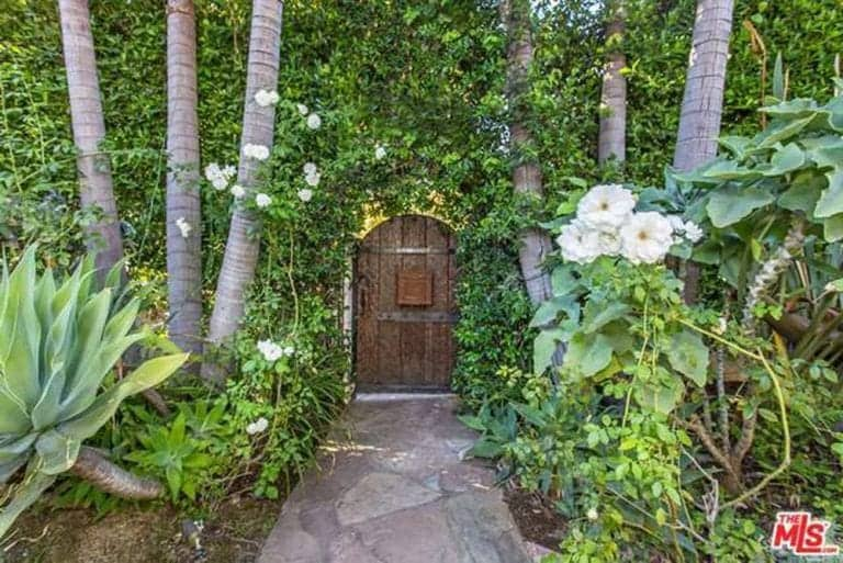 This fantastical scenery gives the small wooden door an effect of being a gateway to a magical place. The overgrown plants, white flowers, and trees that form a corridor enhance this effect and at the same time, provides privacy. The stone texture of the walkway pairs well with the greenery and the wooden garden gate.