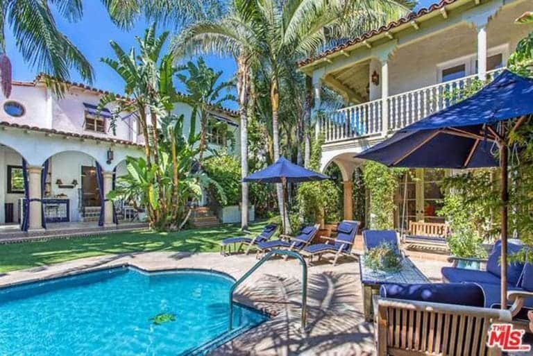 This Spanish landscape presents a tropical paradise that invokes memories of ocean vacations. The bluish umbrellas, cushions of the lawn chairs, and garden sofas complement the blue water of the pool. The tall tropical trees by the poolside and lawn augment the overall aesthetic.