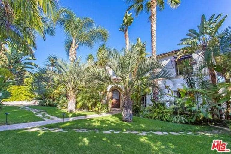 This is a well-manicured grass lawn that is dominated by various palm trees that transport you to a tropical retreat. A main stone walkway leading to the main door is lined by ground lights. It is crossed with paved stone steps embedded into the grass lawn.