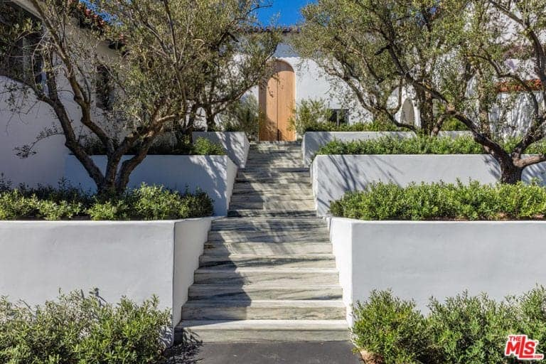 A marble stairway passes through the middle of three-tiered terraces. The stairway leads the way to a zen arched wooden door that complement the six gnarled trees flanking the stairway. Bushes were added to surround the trees and provide an attractive contrast to the white terraces.