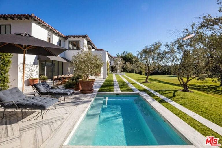 The lawn chairs provide a good vantage point to enjoy the scenery of the pool and wide grass lawn with evenly-spaced trees. The gnarled branches of the trees are a contradiction to the straight white lines of the walkway surrounding the pool.