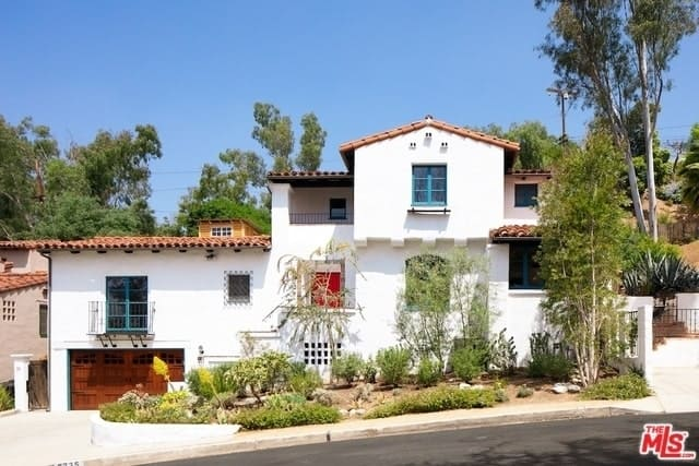The simple and white walls of this Spanish-style home is contrasted with dashes of color with its bluish French windows and doors. The clay-tiled roofs match the wooden garage doors and landscaping that present a romantic Spanish scenery.