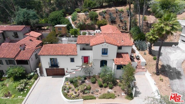 The centerpiece of this lovely Spanish home is its brilliant reddish wooden main door that adds a romantic personality to the traditional elements. It overlooks the garden that has tall trees and shrubs that mimic a Spanish locale.