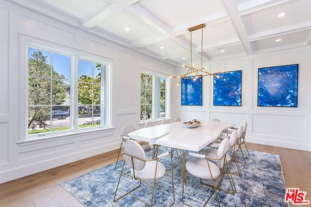 Transitional-style dining room with coffered ceiling, recessed and pendant lighting, windows, and blue paintings on the wall.