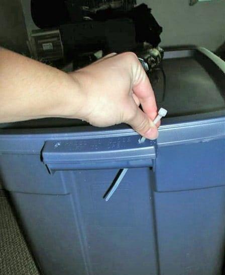 Inserting a zip tie through a storage bin handle.