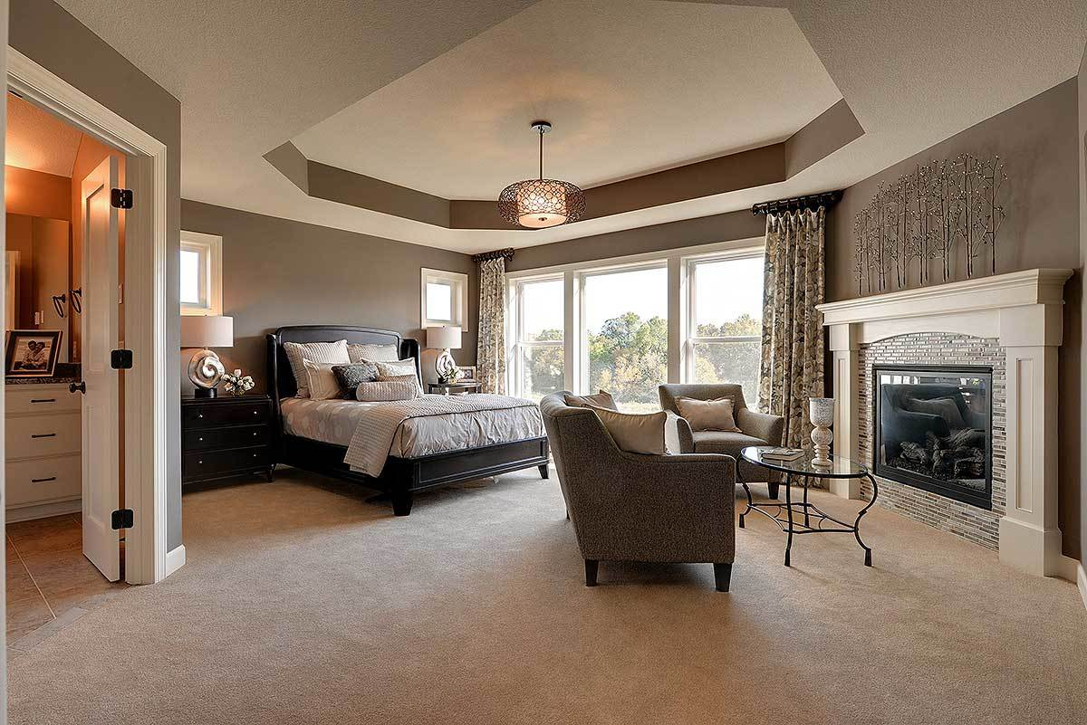 This is a spacious and relaxing bedroom with a large black tufted bed flanked by dark bedside drawers. There is a sitting area at the foot of the bed that has a couple of cushioned armchairs facing a fireplace and topped with a gray tray ceiling.