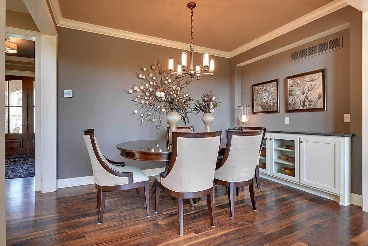 The elegant elliptical wooden dining table matches perfectly with the hardwood flooring of this dining area. These are complemented by the warm chandelier and the various decorations mounted on the gray walls.