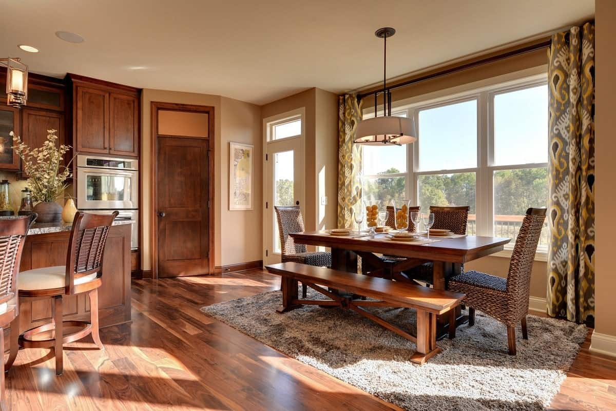 This is a homey and rustic informal dining area with a rectangular wooden dining table paired with a wooden bench and a gray area rug. These are illuminated by the wide set of glass windows on one side.