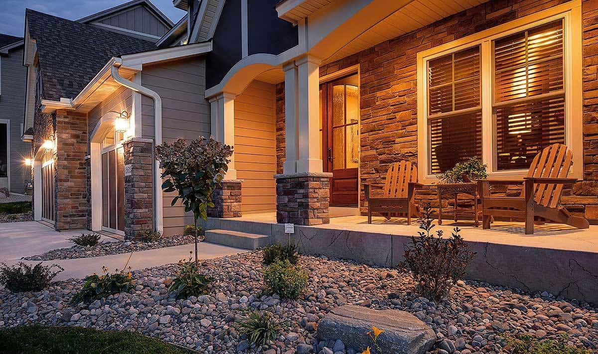 This is a closer look at the front of this lovely house with a pebbled plot next to the grass lawn. This small area has small trees and shrubs illuminated by the warm glow of the front porch.