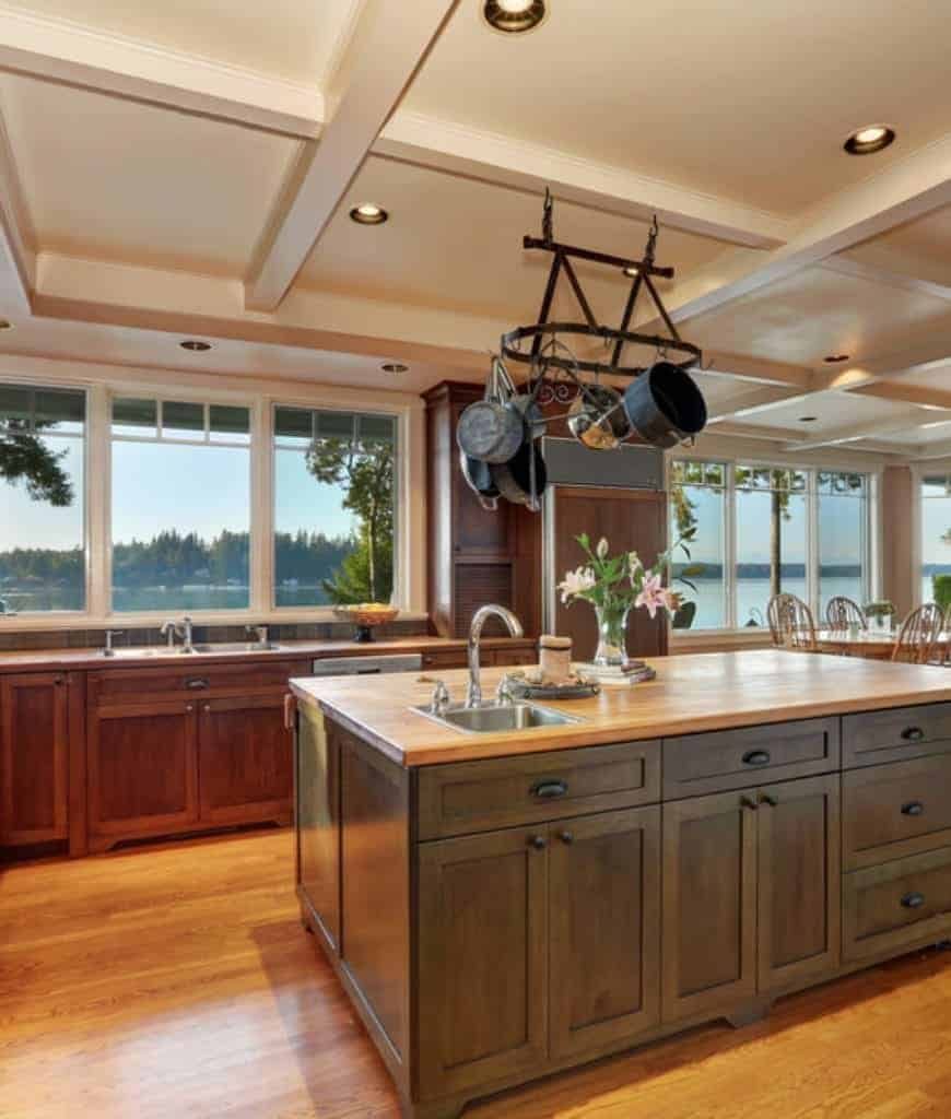 Warm kitchen with wooden cupboard and panoramic windows overlooking a scenic outdoor view. It includes a dark wood breakfast island and vintage pot rack that hung from the coffered ceiling.