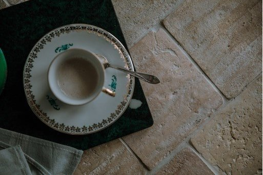 A cup of tea and teaspoon on a saucer placed on reclaimed tile flooring.