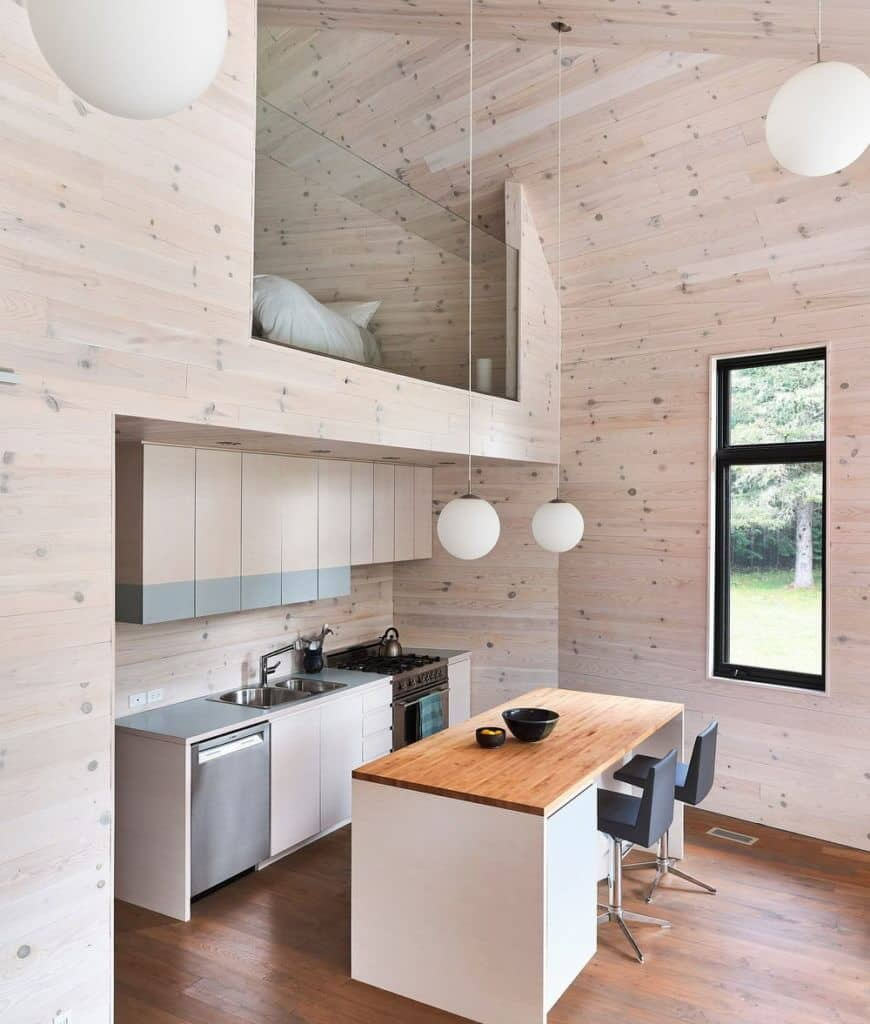 An all wood kitchen illuminated by white globe pendants that hung from the vaulted ceiling. It has wood plank flooring and glazed windows framed with black aluminum.