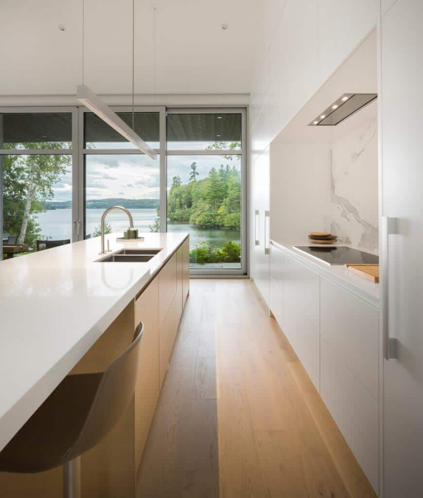 Galley kitchen with hardwood flooring and panoramic windows overlooking a picturesque view. It has white cabinetry and lengthy island bar lighted by a linear pendant light.