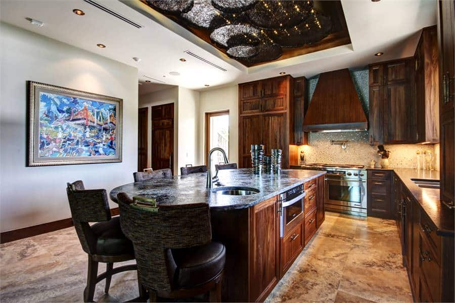 The kitchen has a gorgeous earthy marble flooring and a stunning tray ceiling that matches the tone of the wooden cabinetry and the central island bar paired with wooden stools.