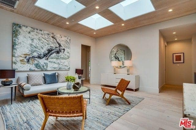 There is a large framed painting mounted on the white wall above the cushioned light gray couch facing a round glass-top table and a couple of rustic woven chairs over a gray area couch and wooden ceiling with four sun roofs.