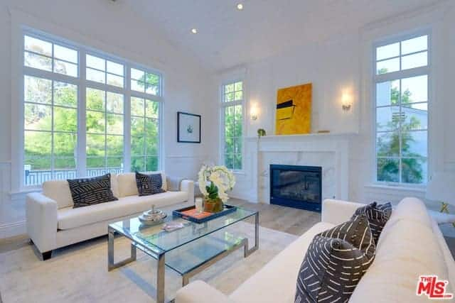 This bright and airy living room has white walls paired with tall windows flanking the white mantle of the fireplace facing the glass-top coffee table in the middle of two white couches paired with a white area rug over the hardwood flooring.