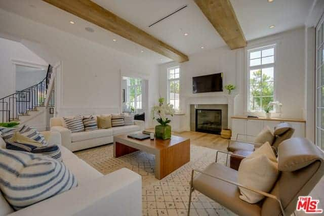 The brilliant white ceiling is contrasted by a couple of large exposed wooden beams that match with the hardwood flooring and the wooden coffee table surrounded white couches and a couple of beige leather cushioned armchairs.