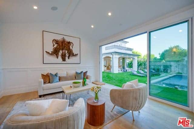 This living room's bright and airy quality is due to the high white cathedral ceiling and the wall-high sliding glass doors illuminating the white sofa set adorned with a wall-mounted painting just above the white wainscoting.