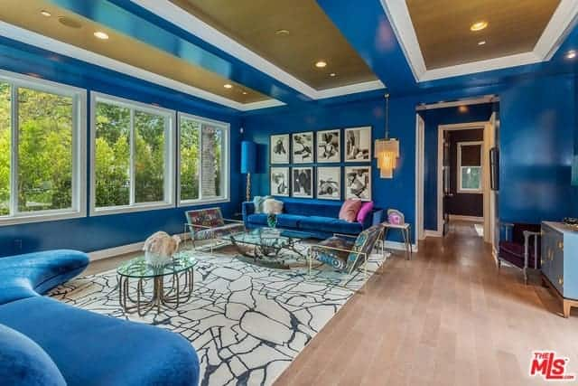 This eclectic blue-walled living room has a matching blue ceiling with golden centers in its trays. The blue walls are also matched with blue sofas over a large white patterned area rug and the hardwood flooring.
