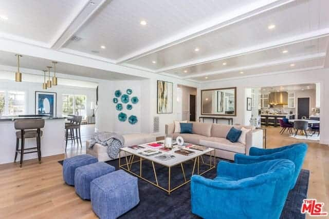 This small living room maximizes its small floor area with a navy blue area rug covering the hardwood flooring. This is topped with a beige couch, blue armchairs and ottomans surrounding a white-top coffee table.