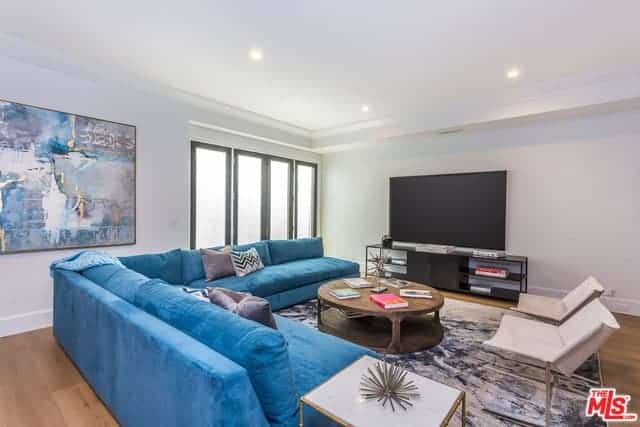 The brilliant white ceiling with pin light are perfectly paired with the white walls that are contrasted by the large TV on the low cabinet with shelves. This is complemented by the blue L-shaped sofa over the gray area patterned rug.