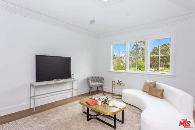This simple living room has a white ceiling and walls contrasted by the TV on a white console table facing the curved white couch and its wood-topped coffee table over the beige area rug of the hardwood flooring.