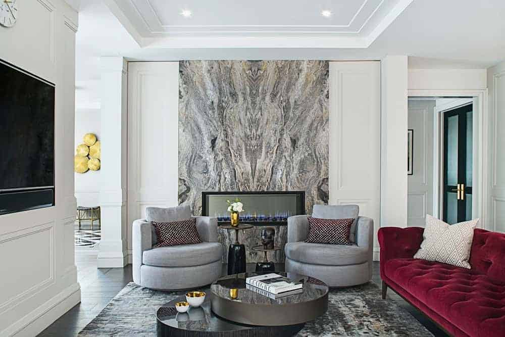 This living room exudes elegance despite its eccentricity. The white tray ceiling is paired with white walls dominated by a large gray marble panel housing the modern fireplace flanked with gray armchairs and a red velvet cushioned sofa facing a modern two-tier coffee table.