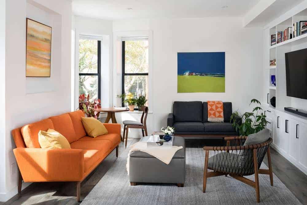The white walls and white ceiling are adorned with dashes of color from the pair of wall-mounted paintings and the orange sofa facing the TV housed in a white wooden structure with cabinets and shelves.