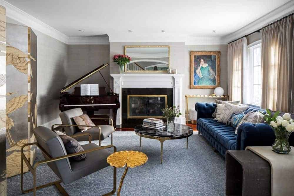 This elegant living room has a piano in the corner beside the white mantle of the fireplace that has a glass covering that is perfectly paired with the mounted mirror with golden frames as well as the classical painting in the corner by the blue couch.