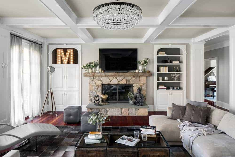 The beige stone structure that houses the fireplace is a nice complement to the light gray walls and tray ceiling with a brilliant crystal lighting over the glass-top coffee table by the light gray L-shaped sofa and its gray patterned area rug.