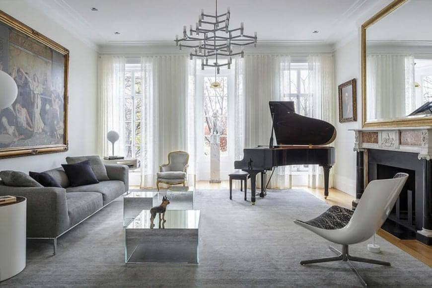 The modern white chandelier hanging over the modern glass coffee table is a nice contrast to the classical grand piano paired with a fireplace with an elegant mantle with a golden framed mirror across from the classical painting over the gray sofa.