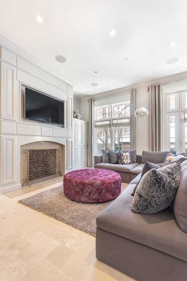 This is a charming and elegant white living room white its fireplace housed in a white wooden structure that also supports the mount of the TV facing the Gray L-shaped sectional sofa with a round cushioned ottoman for a coffee table.