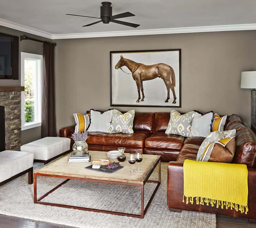 The large L-shaped brown leather sofa is perfectly complemented by the wall-mounted framed painting of a brown horse on the gray wall contrasted by the white ceiling and its black ceiling fan over the wood-top coffee table.